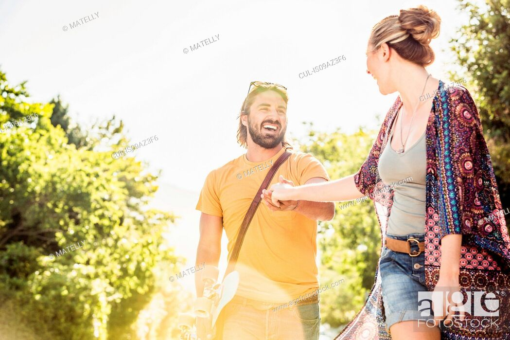 Stock Photo: Happy young couple holding hands in park, Franschhoek, South Africa.