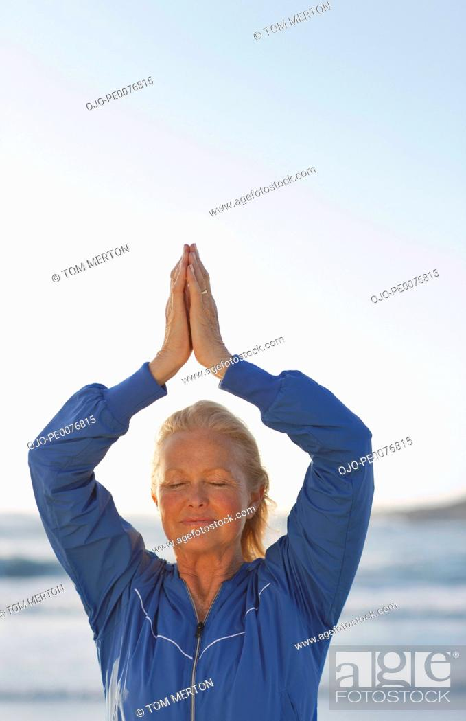 Stock Photo: Woman standing with hands clasped overhead.