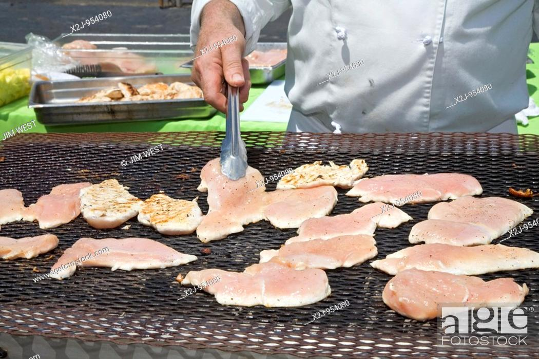 Stock Photo: Livonia, Michigan - A caterer prepares chicken on an outdoor grill.