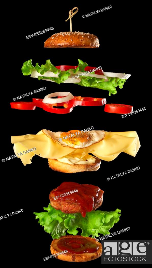 Stock Photo: big tasty burger with meat cutlet, cheese, fried egg, tomatoes, cucumber pieces and green lettuce, fast food levitates, black background.