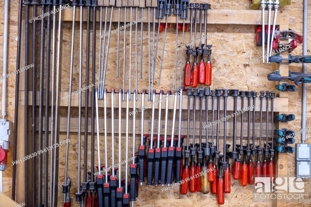 "Stock Photo: 22 June 2020, Mecklenburg-Western Pomerania, Rostock: Screw clamps are hanging in the workshop """"Historical keyboard instruments - Johann-Gottfried Schmidt""""."