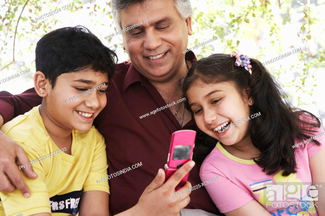 Stock Photo: Close-up of a grandfather and his grandchildren looking at a mobile phone.