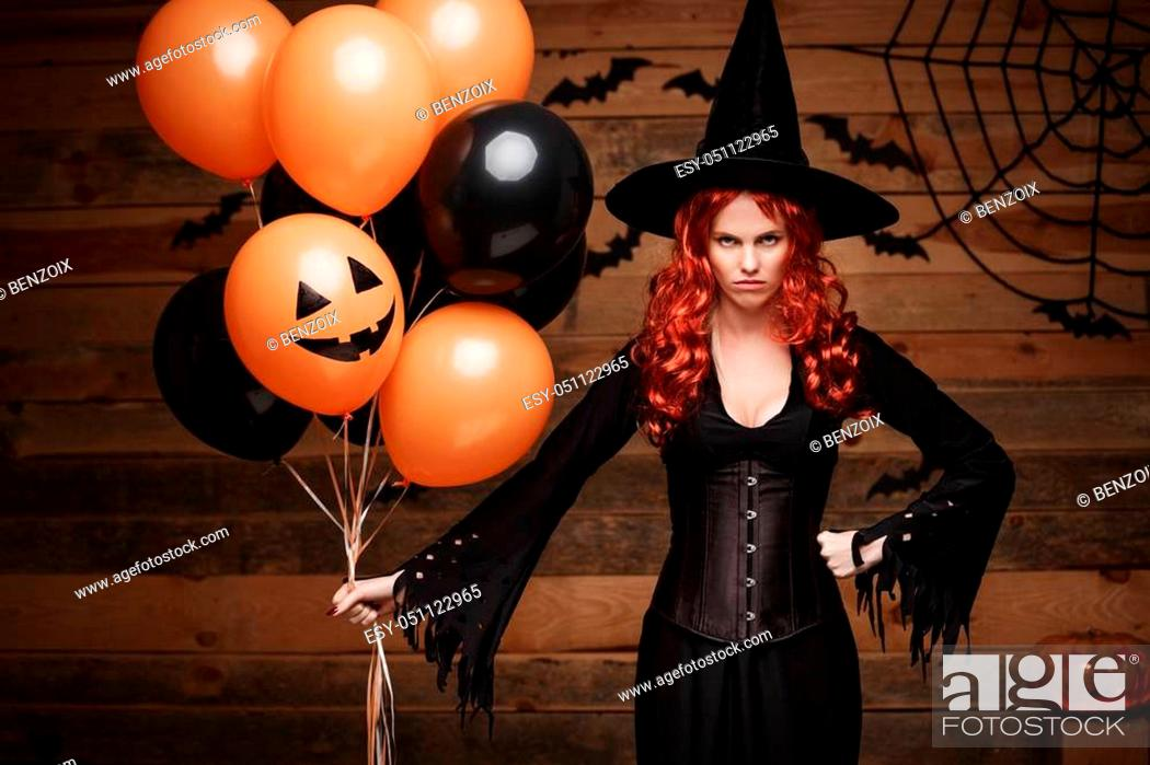 Stock Photo: Halloween Witch Concept - Beautiful caucasian woman in witch costumes celebrating Halloween posing with posing with orange and black balloon over bats and.