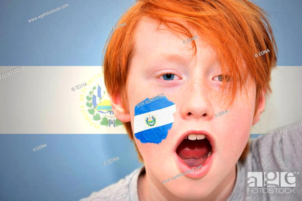 Photo de stock: redhead fan boy with salvadoran flag painted on his face. on the salvadoran flag background.