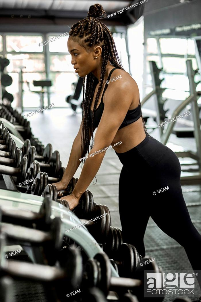 Stock Photo: Female athlete choosing weights for training in gym.