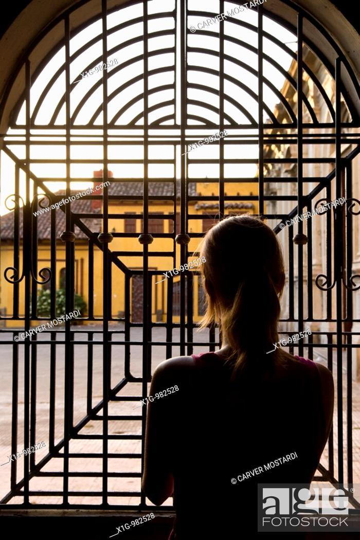 Stock Photo: Woman staring out of iron window at the Iglesia de la Merced, Granada, Nicaragua.
