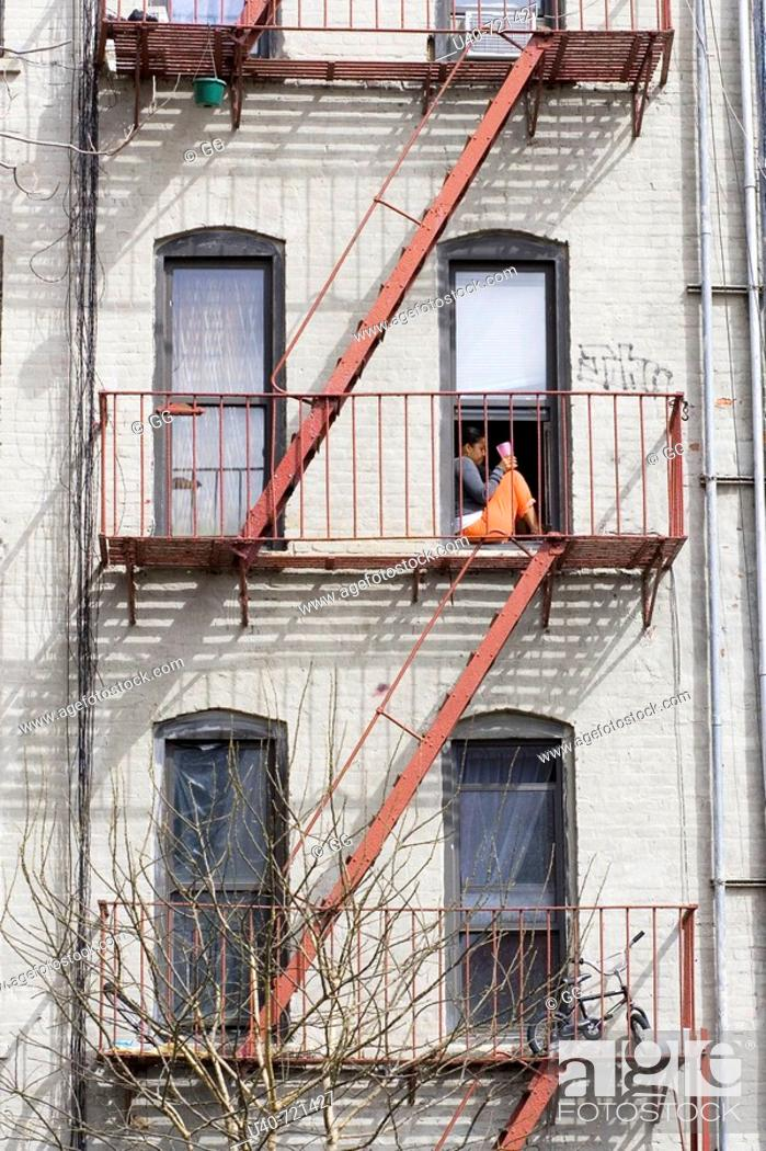 Stock Photo: Woman sitting on fire escape, NYC, USA.