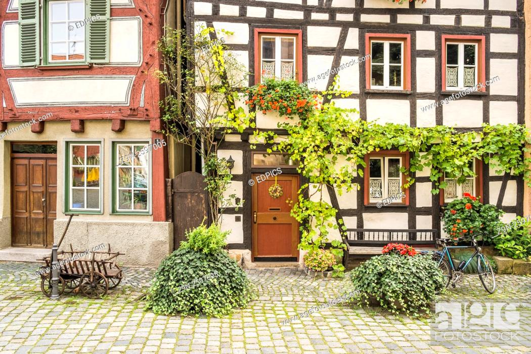 Stock Photo: bicycle and historic hand waggon in front of the flowerdecked facade of half timbered houses in the historic part of esslingen, baden-wuerttemberg, germany.