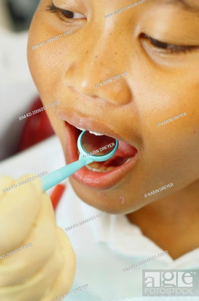 Stock Photo: Close up of dentist's hand holding dental mirror in boy's mouth.