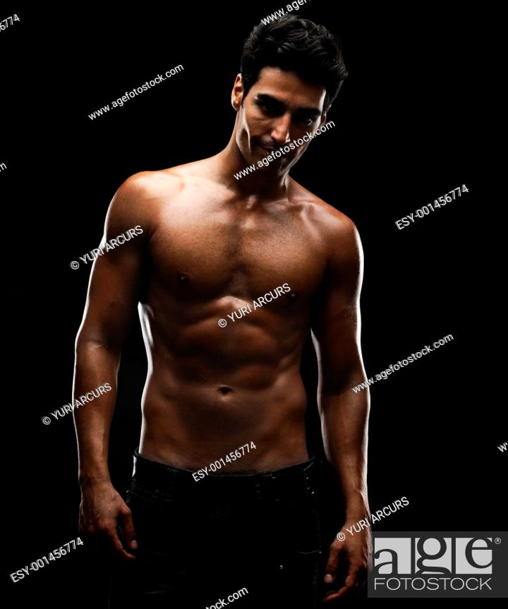 Stock Photo: Portrait of a sexy young man with a cute smile against black background.