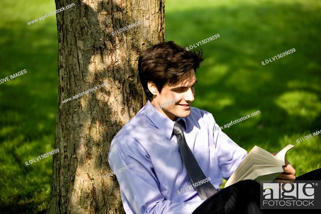 Stock Photo: A businessman leaning against a tree, reading a book.