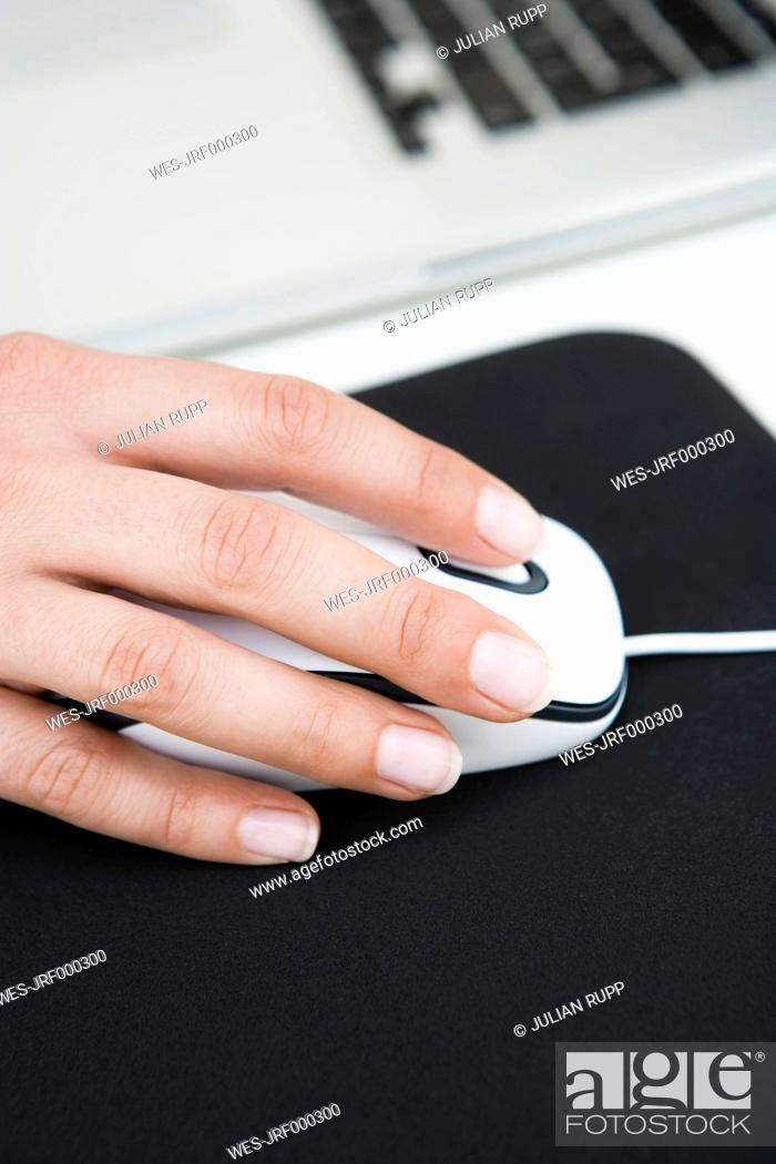 Stock Photo: Germany, Bavaria, Diessen am Ammersee, Close up of woman's hand on mouse with mousepad.