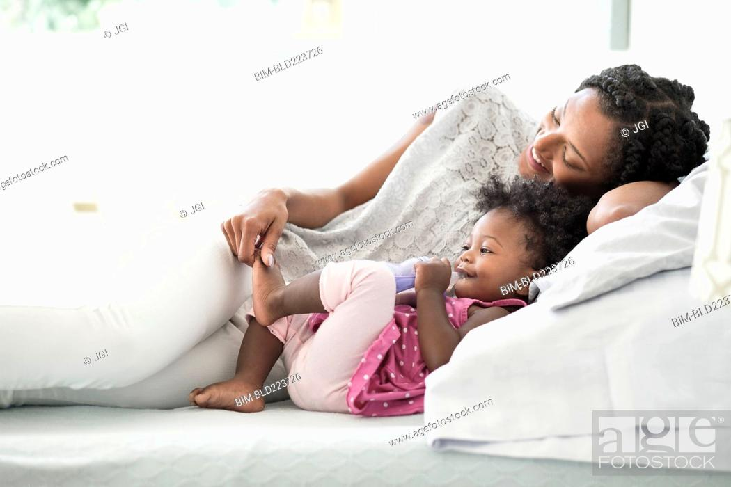 Stock Photo: Black woman playing with foot of baby daughter on bed.