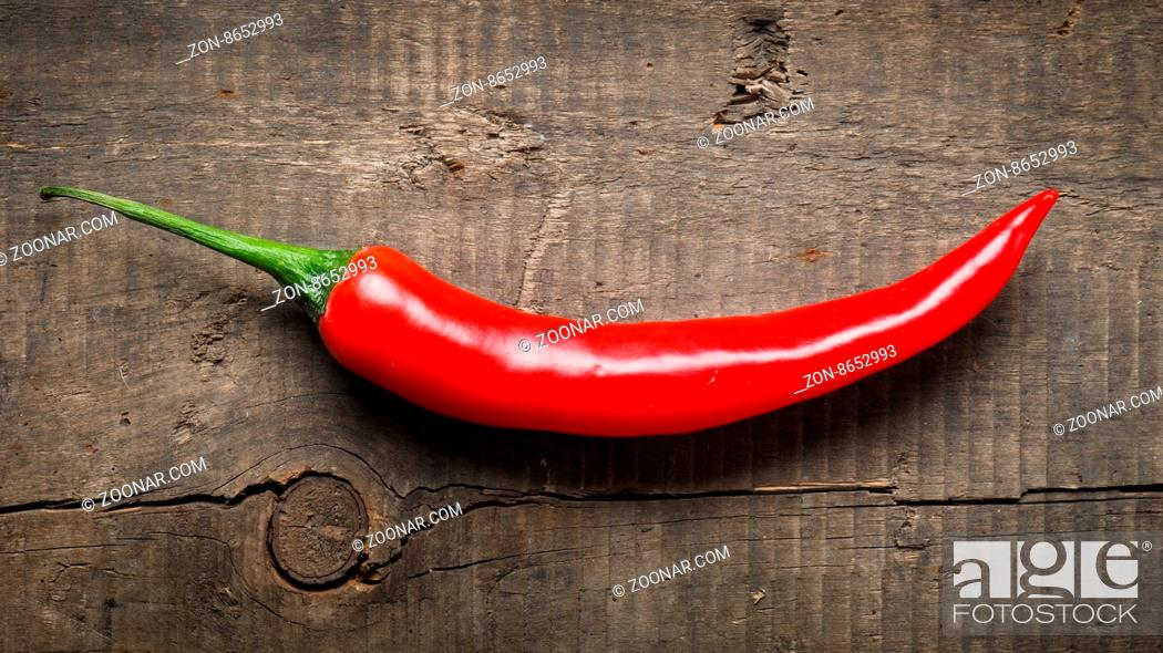 Stock Photo: Red chili on an old used wooden table.