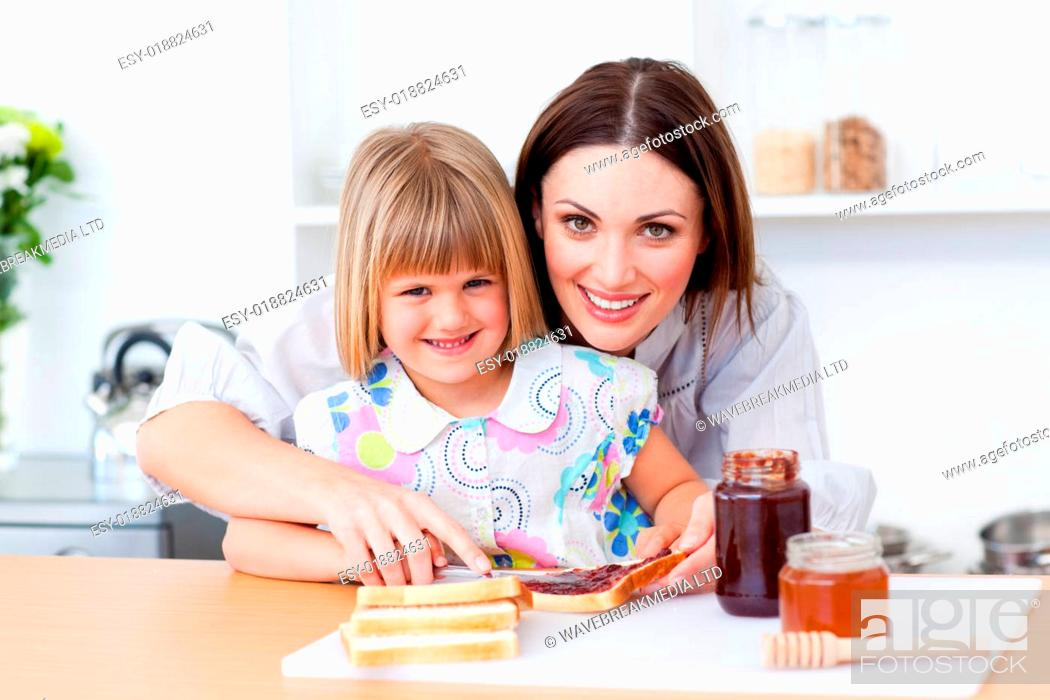 Stock Photo: Attentive mother helping her daughter prepare the breakfast.