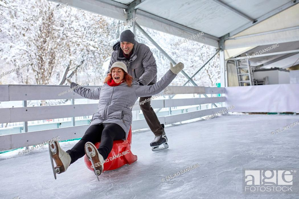 Stock Photo: Couple ice skating, using seal sledge to push woman.