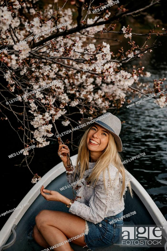 Stock Photo: Japan, Tokio, Chidorigafuchi Park, smiling woman in rowing boat at cherry tree blossom.