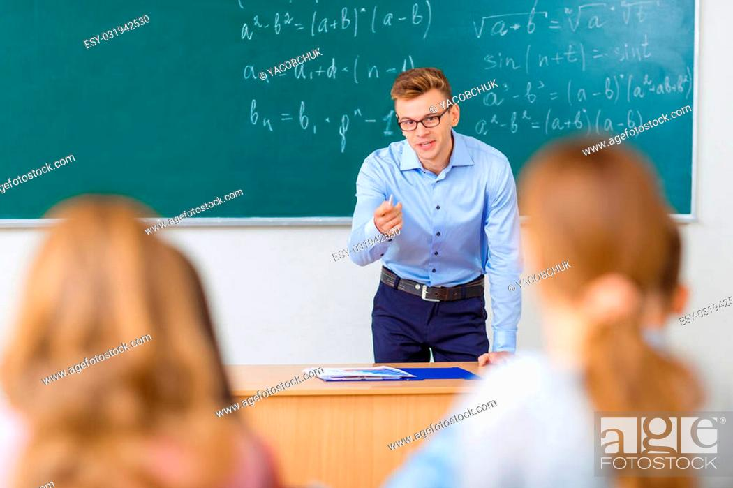 Stock Photo: Thorough explanation. Young male college professor is busy with explaining the lecture he has given.