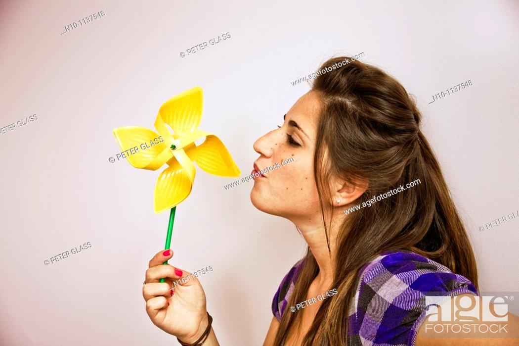 Stock Photo: Teen girl blowing on a pinwheel.