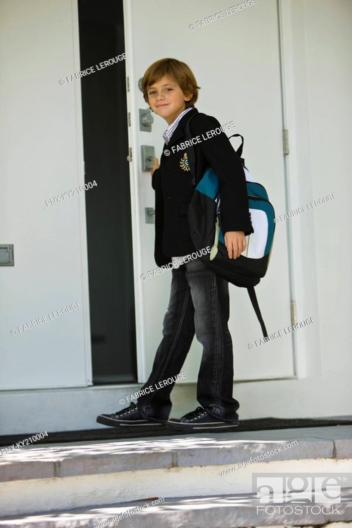 Stock Photo: Portrait of a schoolboy opening the door of a school.