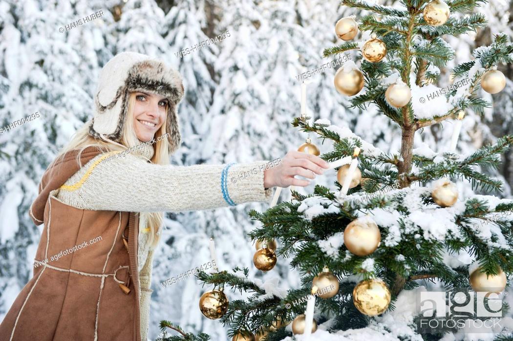 Stock Photo: Austria, Salzburg County, Mid adult woman lighting candle on Christmas tree, smiling, portrait.