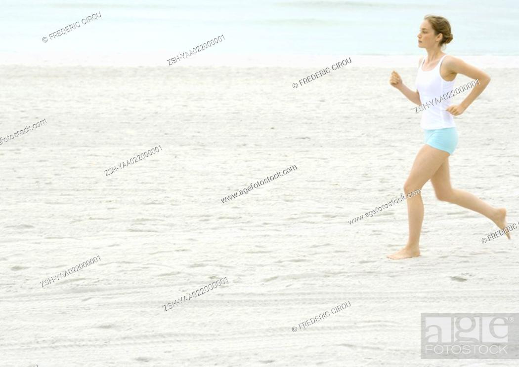 Stock Photo: Young woman running on beach.
