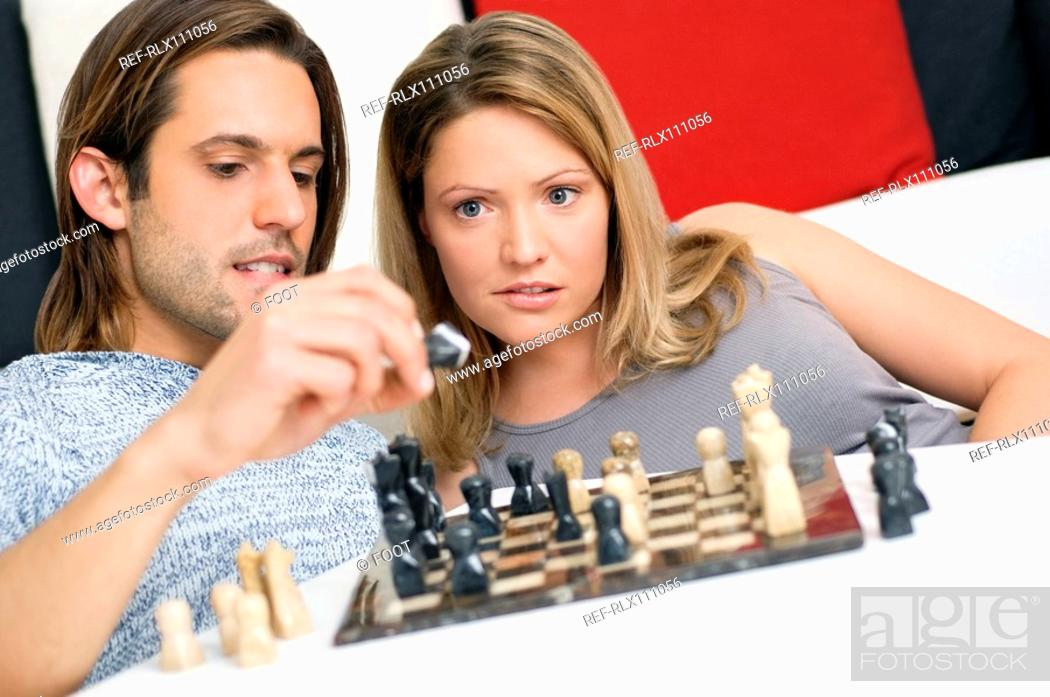 Stock Photo: Young couple playing chess.