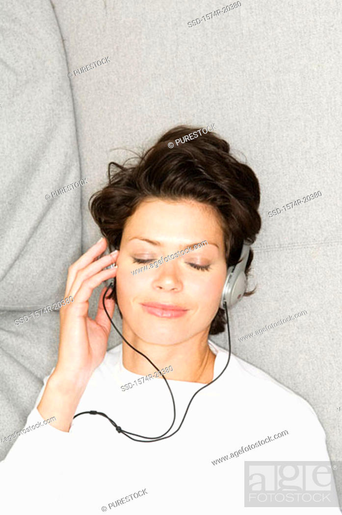 Stock Photo: High angle view of a young woman wearing headphones and listening to music.
