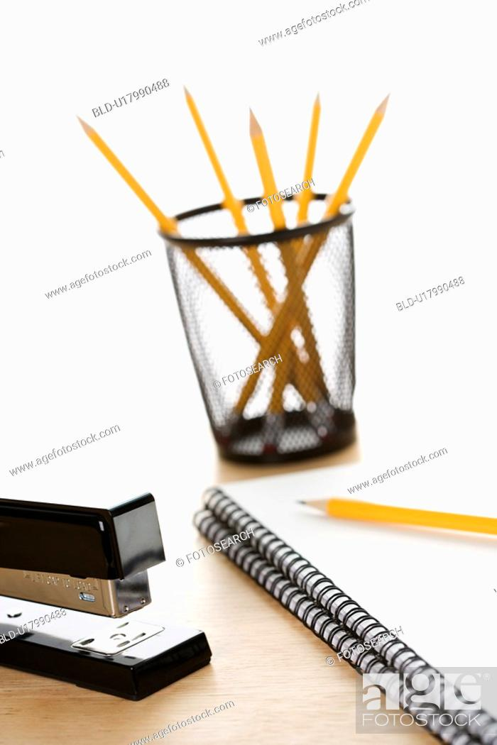 Stock Photo: Pencils, a stapler, and spiral bound notebooks arranged on a desk.