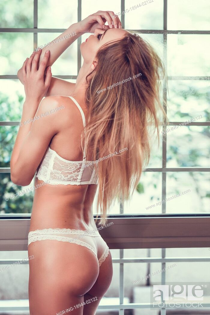 Stock Photo: Beautiful blonde woman in white lingerie posing near a window. Young girl wearing underwear with long hair.