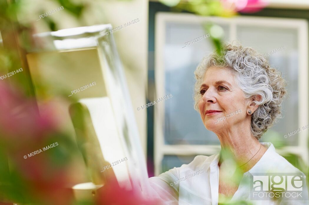 Stock Photo: Senior woman painting on canvas at porch.