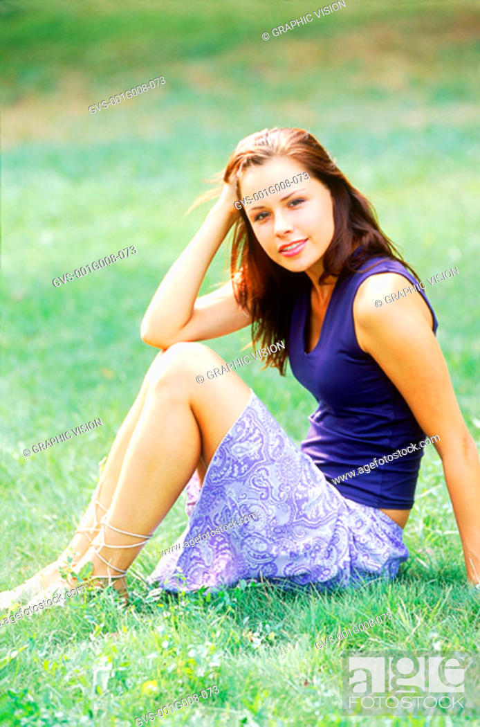 Stock Photo: Portrait of a woman sitting in a lawn.