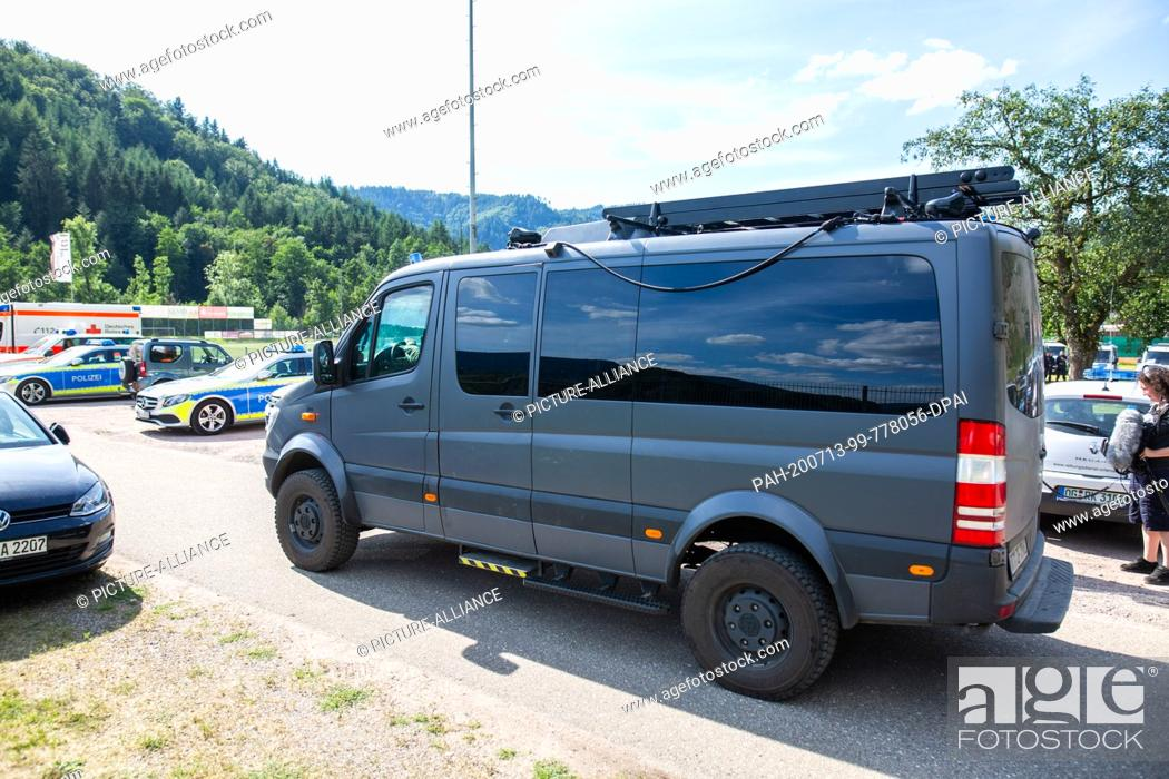 Stock Photo: 13 July 2020, Baden-Wuerttemberg, Oppenau: A SEK vehicle drives over the parking lot of a sports field, which serves as a meeting point for the police.