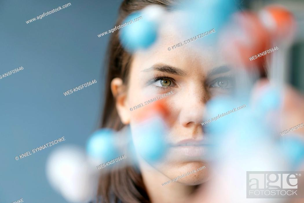 Imagen: Female scientist studying molecule model, looking for solutions.