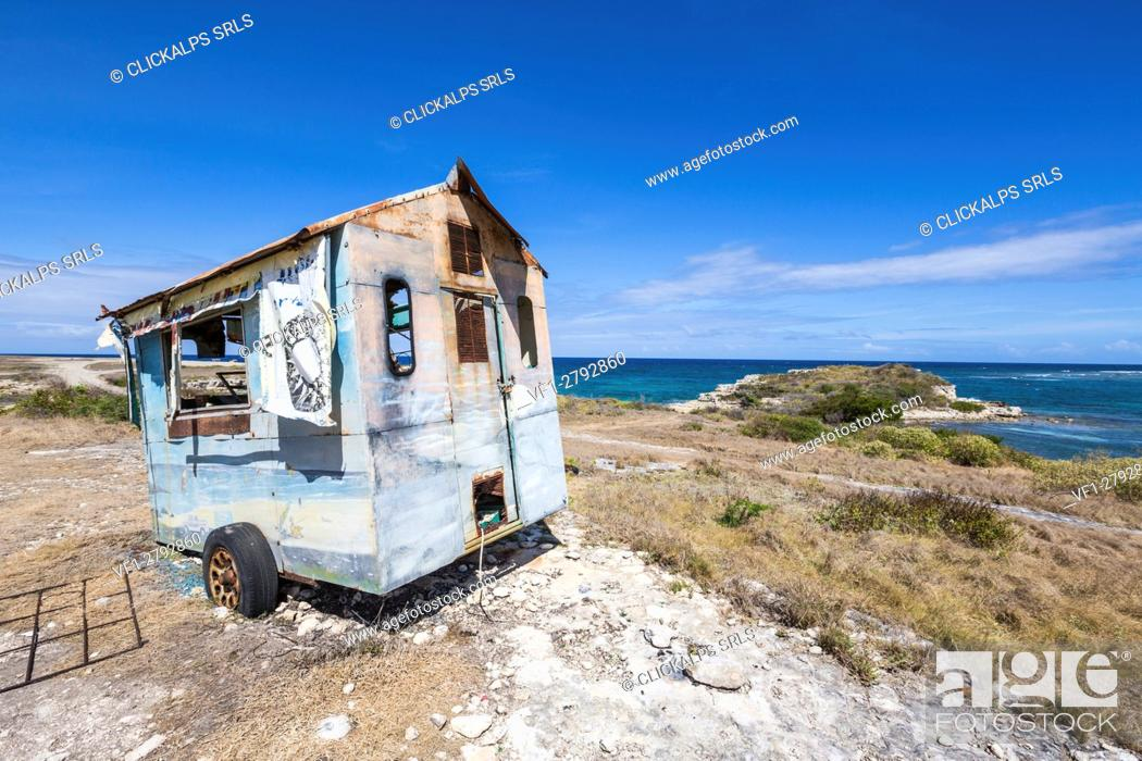 Stock Photo: An abandoned roulotte frames the blue sea around the cliffs of Devil's Bridge Antigua and Barbuda Leeward Islands Antilles.