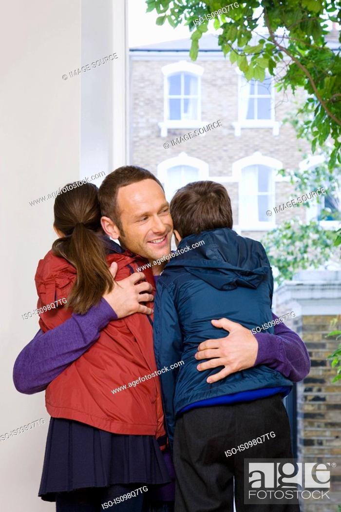 Stock Photo: Father hugging son and daughter.