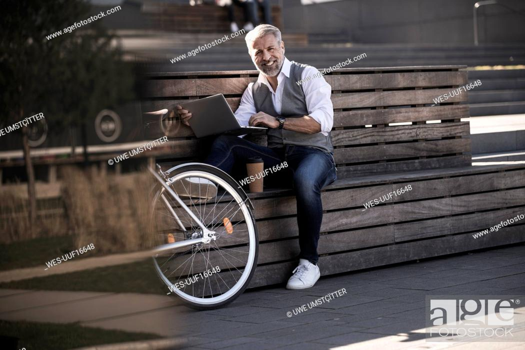 Stock Photo: Smiling mature businessman with bicycle sitting on a bench using laptop.