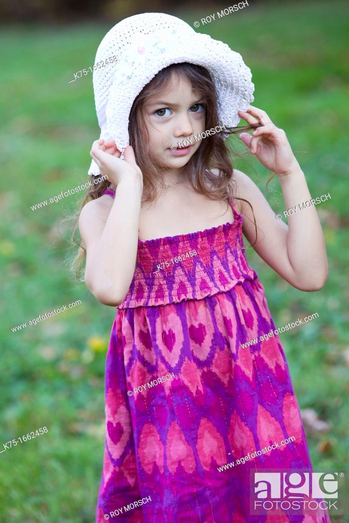 Stock Photo: Little girl holding her hat on her head.