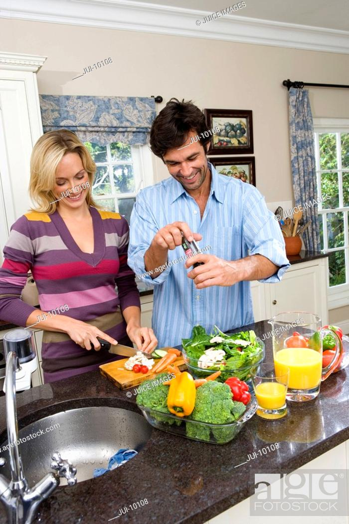 Stock Photo: Young man and woman making salad by jug of juice, smiling.