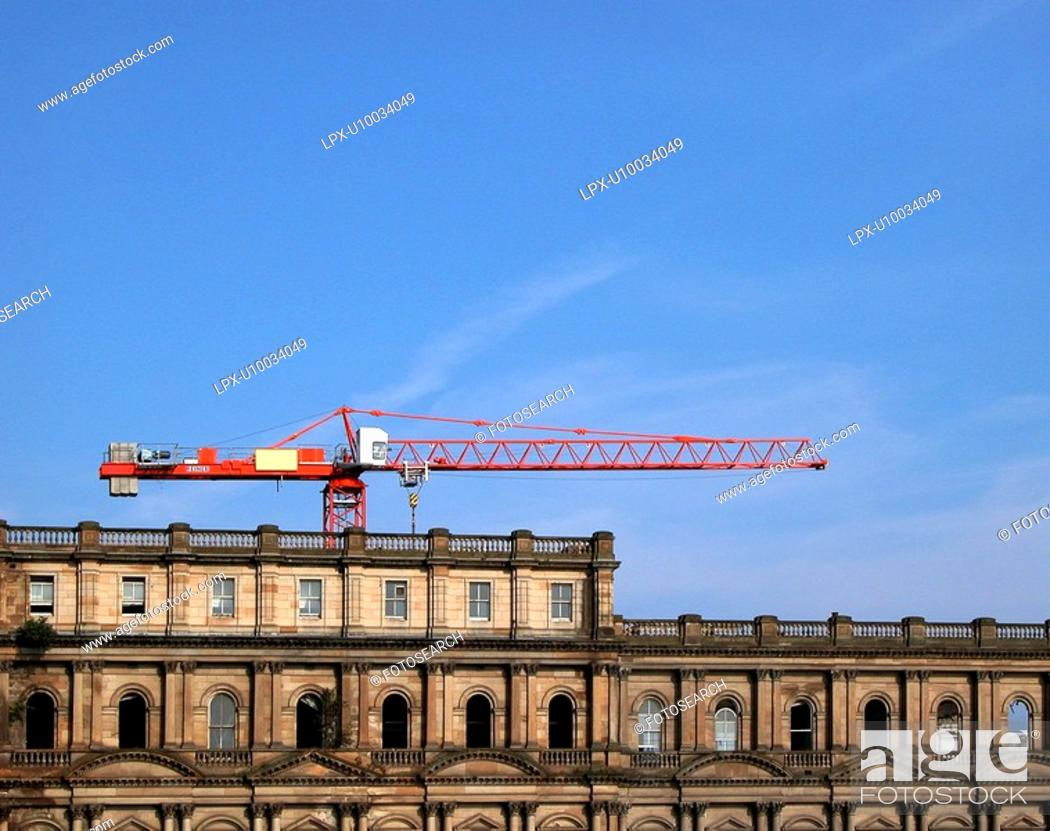 Stock Photo: Retained facade of big building with red tower crane protruding above.