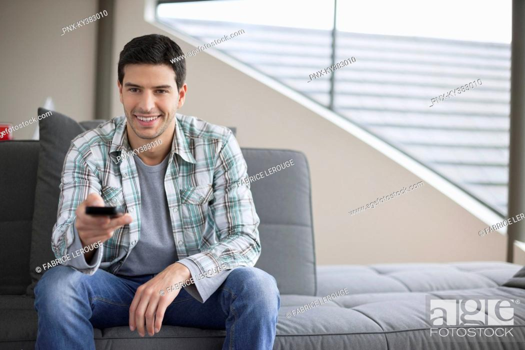 Stock Photo: Man changing channels with a remote control.