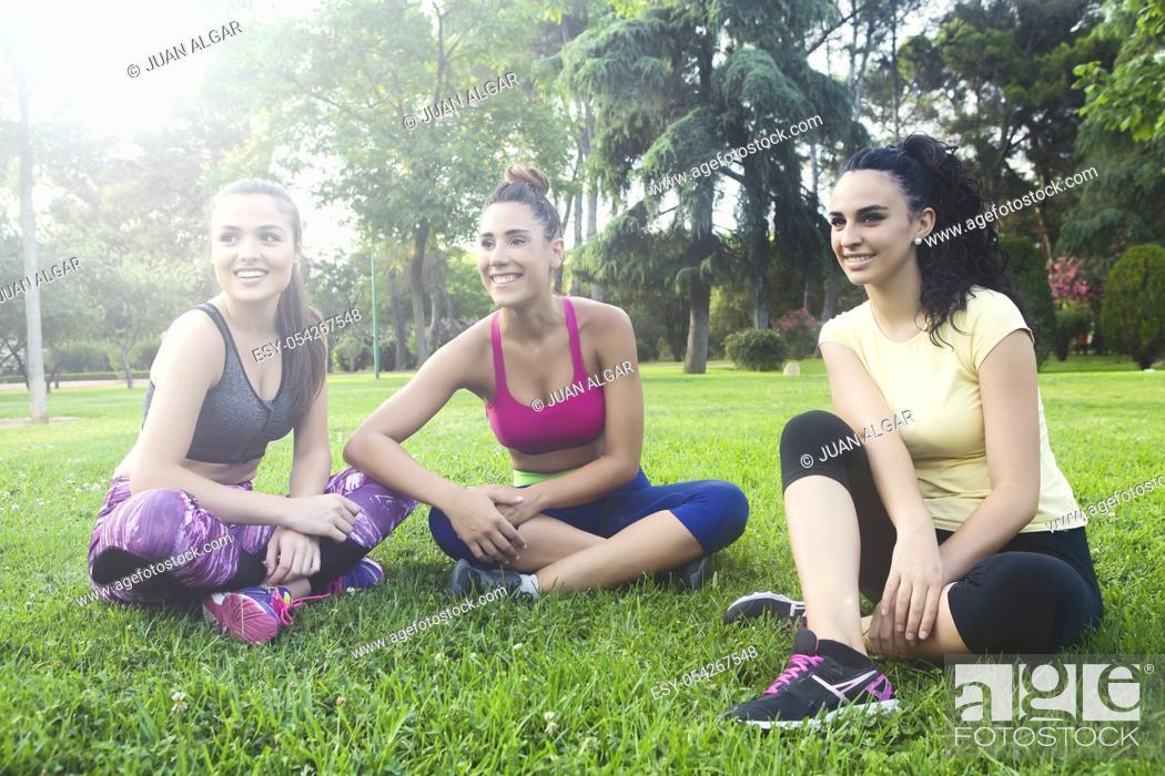 Stock Photo: Happy sportswomen sitting with crossed legs on grass in park.
