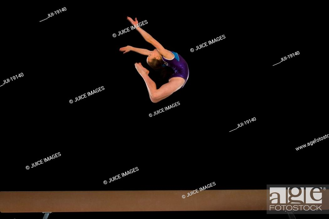 Stock Photo: Young female 10-12 gymnast performing in air above balance beam, side view.