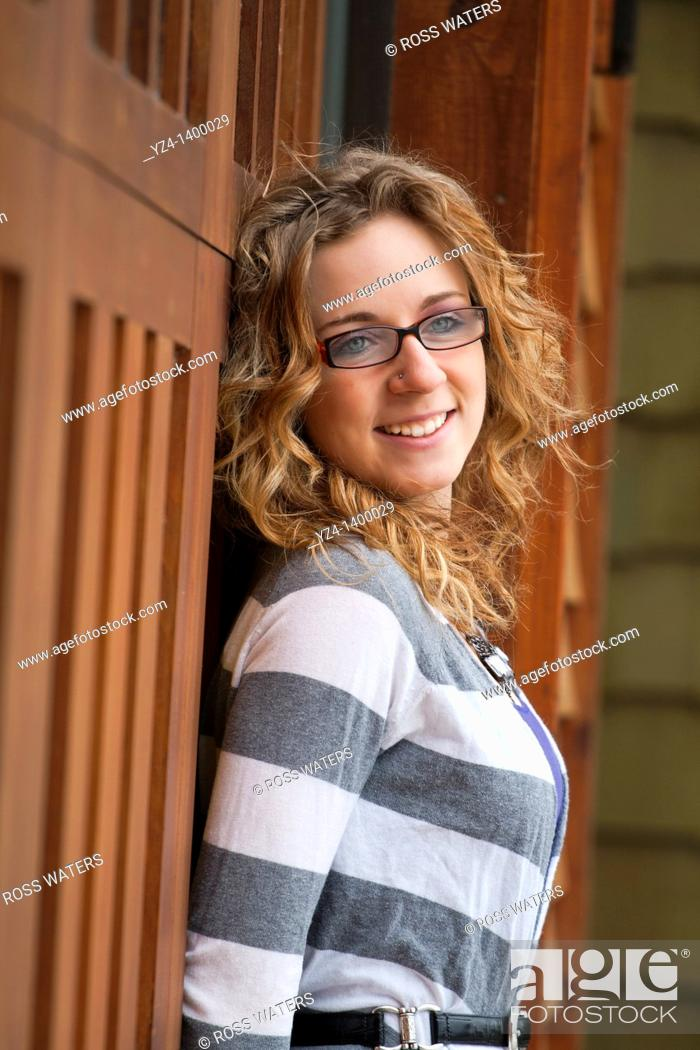 Stock Photo: A young woman outdoors by a house.