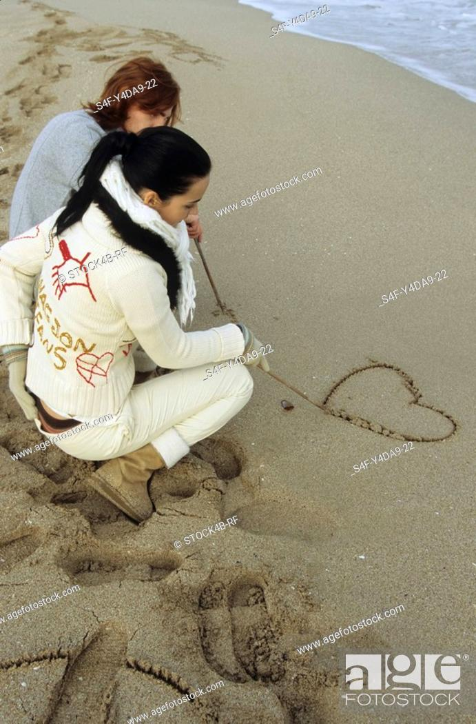Stock Photo: Young Man with auburn Hair drawing a Heart into the Sand with a Stick - Symbol - Love - Relationship - Beach - Coldness - Season.