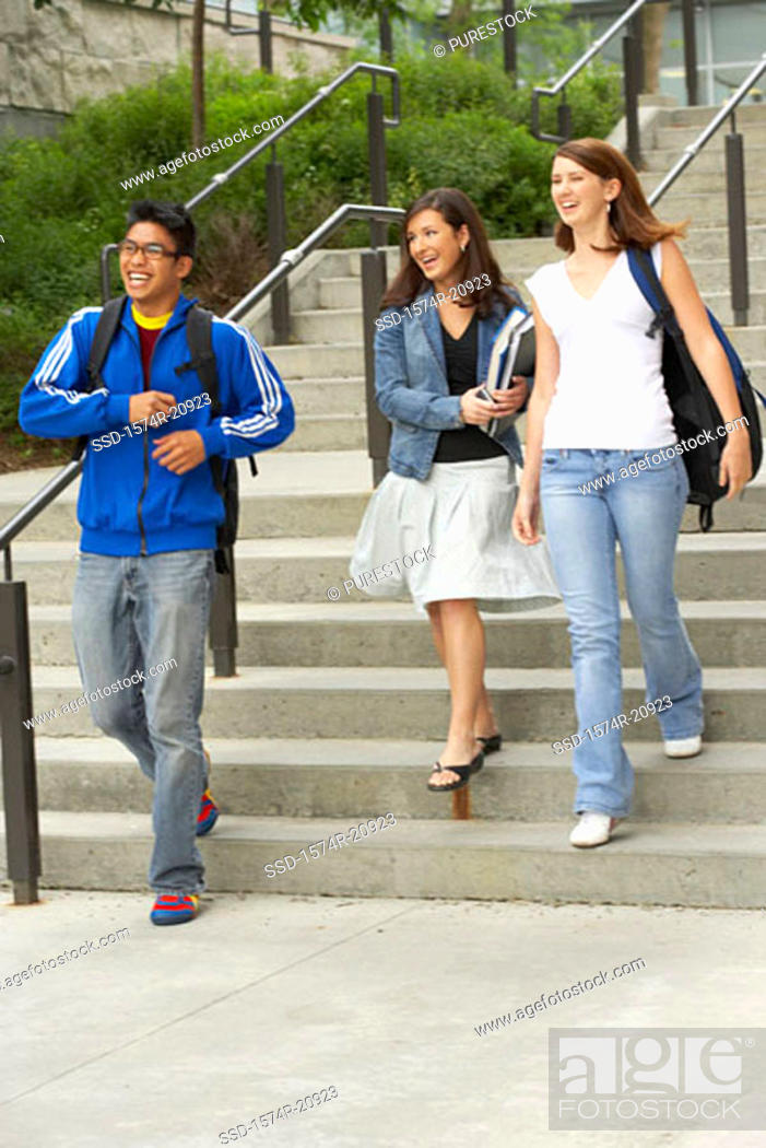 Stock Photo: Three college students moving down a staircase and smiling.