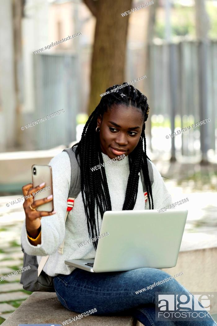 Stock Photo: Female student using laptop and cell phone on a bench.