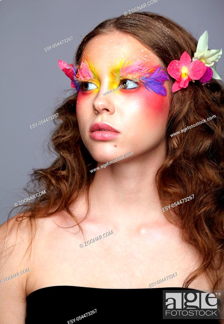 Imagen: Portrait of teen girl with orchid flower in wavy hair. Young female with unusual stylish make-up and false fashion feather eyelashes.