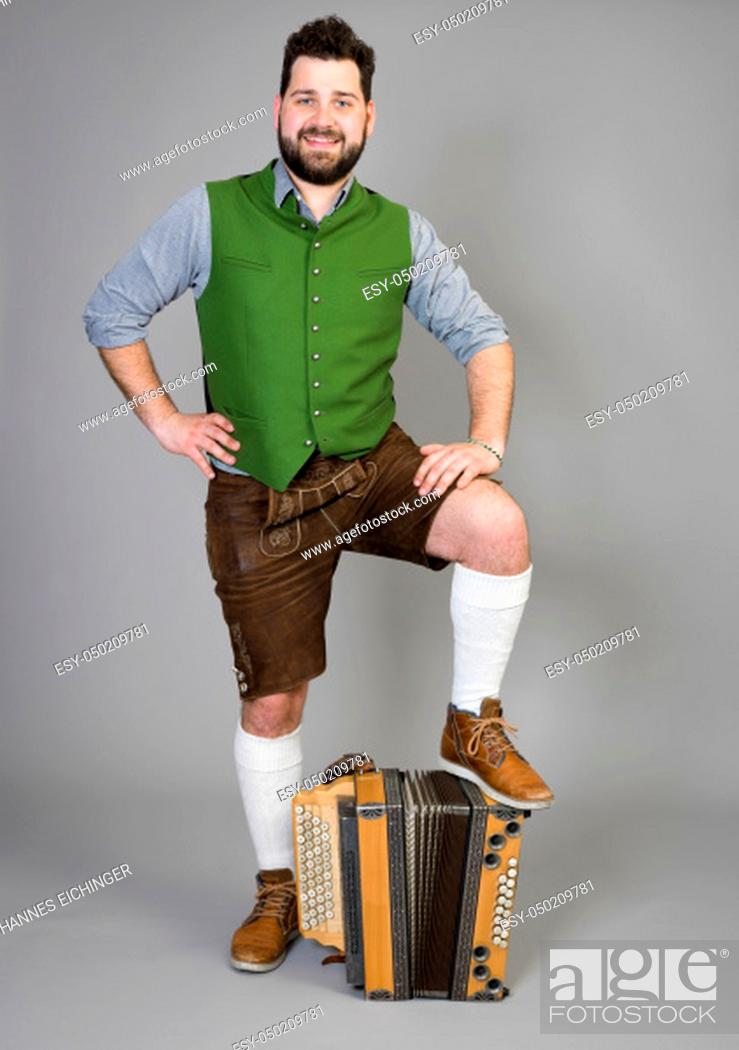 Stock Photo: young man with black beard and leather trousers and traditional costume and accordion is posing in front of grey background.