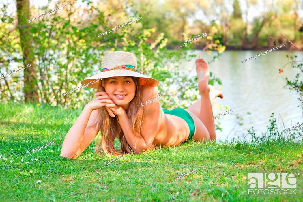 Stock Photo: young blond girl with a hat lying on the grass.